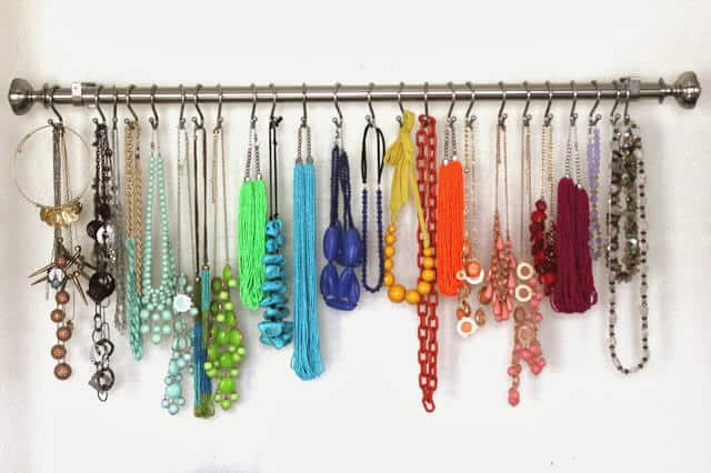 Curtain rail on the wall with hooks for necklaces